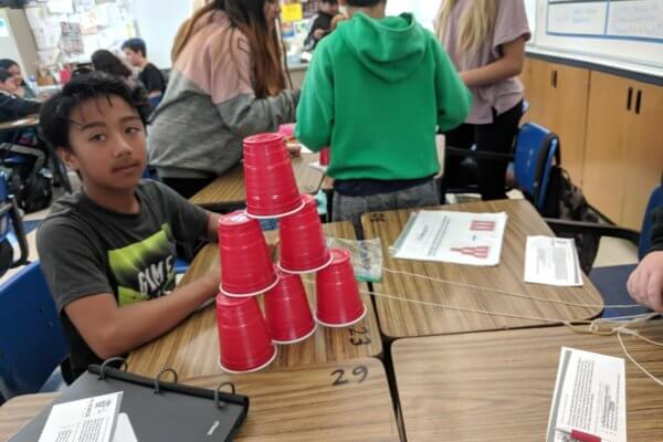 A student sits behind a pyramid of solo cups.