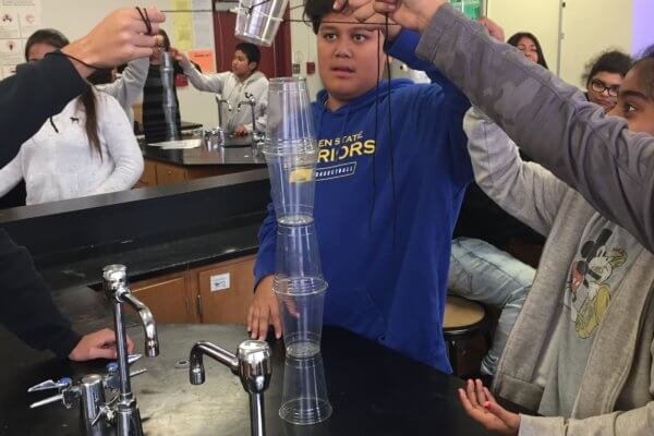 Students use strings and elastics to try to stack cups on top of each other.
