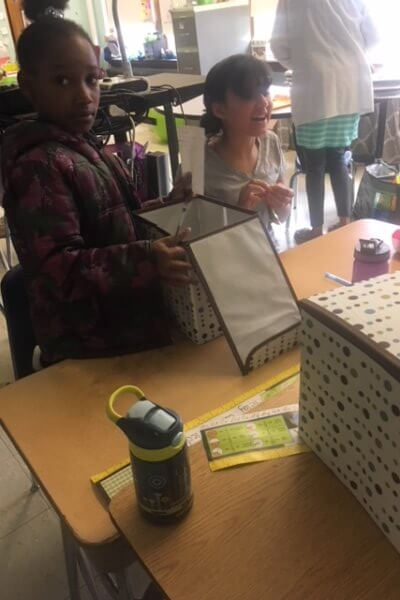 Student looks in a box as part of the observation challenge.