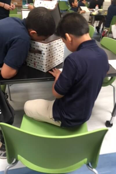 One student taking notes, while the other is looking inside a box.
