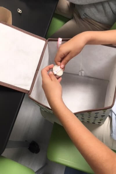 Student pulling a measuring tape out of a box.
