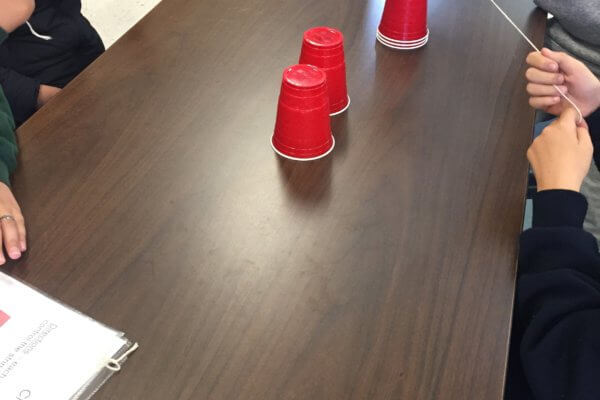 A table is shown with students using string to stack red solo cups.