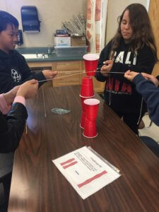 Students using string to place red solo cups on top of each other.