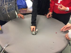 A fabric circle is shown with a rock in the middle and marbles moving toward the rock.