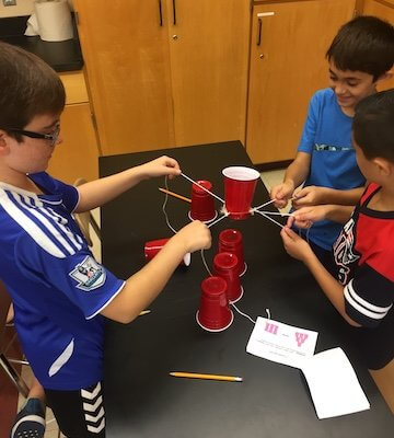 Students work with strings to stack red solo cups on top of each other.