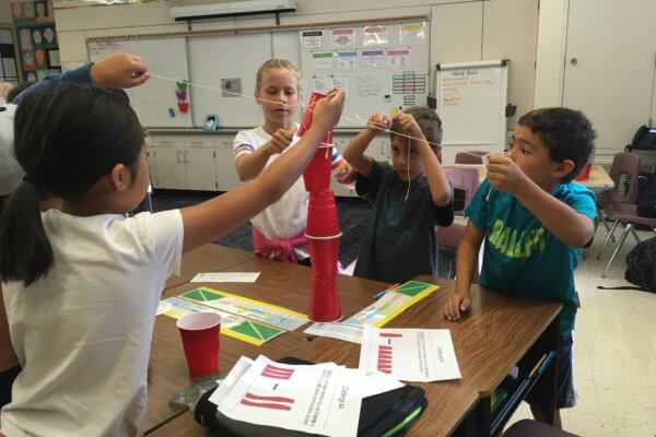 Group of students work in a team with yarn and cups to stack the cups.