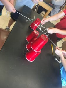 Students stack cups using only strings and an elastic.