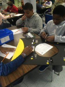 A student is adding pin pong balls to a card board model of the phases of the moon.