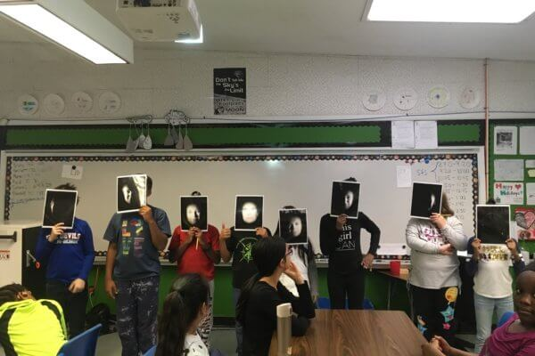 Students stand at the front of the class holding pictures of a face depicting the phases of the moon.