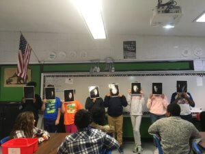 Students stand at the front of the class holding pictures of a face depicting the phases of the moon..