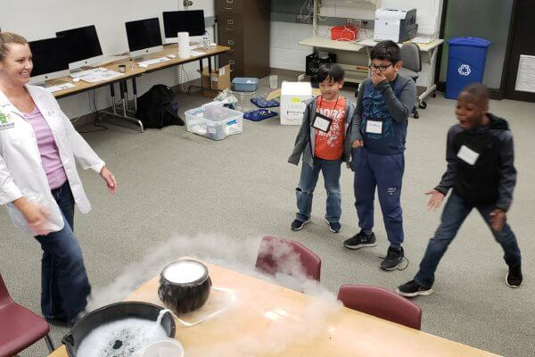 Students watch as instructor creates a dry ice bubble.