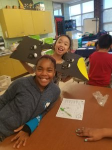 Students wear a cardboard cutout to learn about the phases of the moon.
