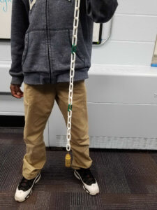 A student holds a chain with weights on the end.
