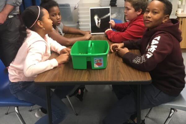 Four students sit at a table looking at a photo of a face.