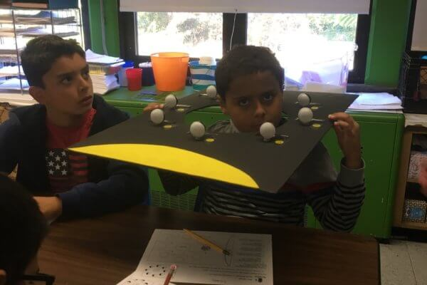 A students has the model of the phases of the moon over his head.
