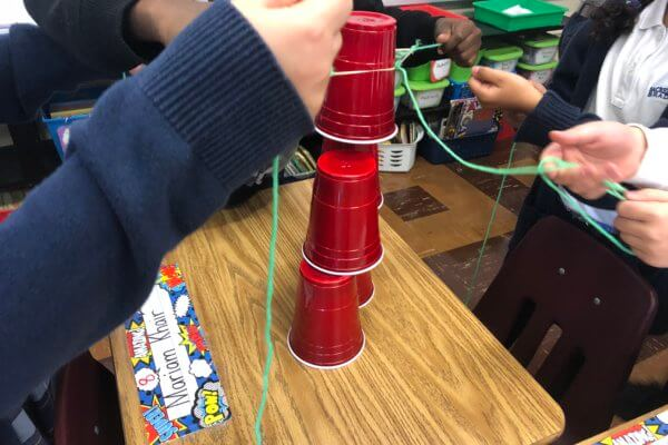 Students use string and an elastic to stack cups on a desk.