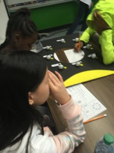 Students work at a table looking at a model of the phases of the moon.