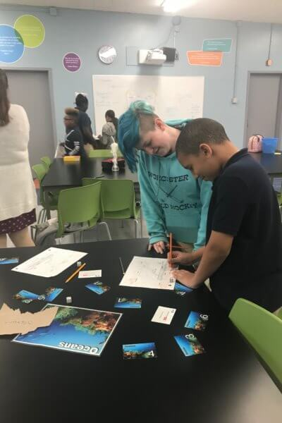 Two students work filling out a worksheet at a table.