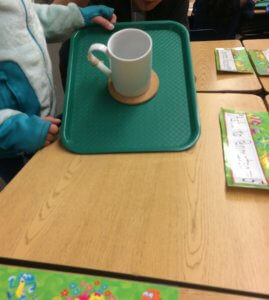Students tilt a cup on a tray.