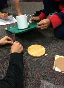Students use a ruler to measure a cup sliding down a tray.