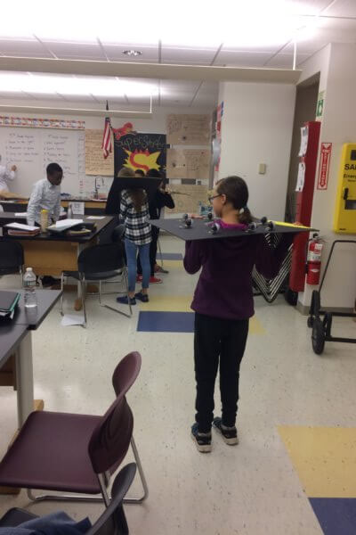 A student stands with the moon phase board over her head while other students look work in the background.