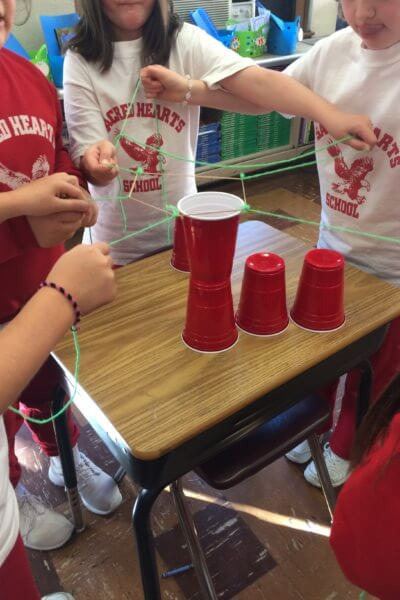 Students use string and elastics to stack cups on top of a desk.