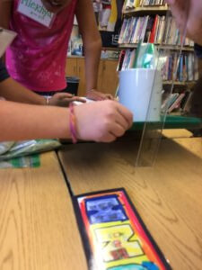 Students tilt a cup on a tray and measure height with a ruler.