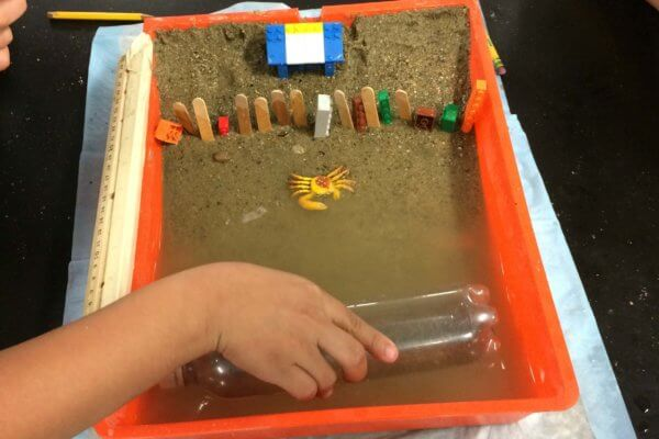 Students create waves with a water bottle in their model beach.