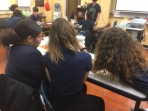 The back of students is shown as they work on their activity at a table.