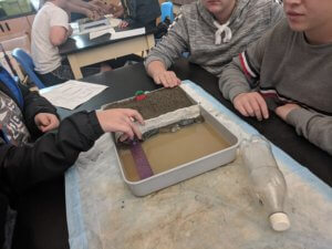 Students working with paint trays to create a model beach erosion barrier.