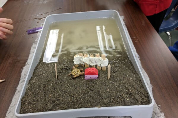 A paint tray is shown that contains a model beach with sand and water.