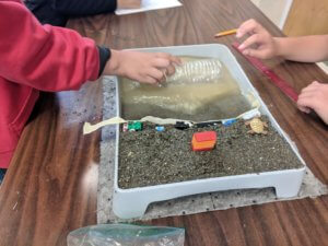 A paint tray is shown that contains a model beach with sand and water while a hand holds an empty water bottle over the water.