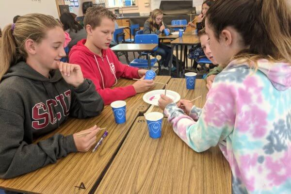 Students use chopsticks to pick up wooden fish from a plate in the center of the desk and drop them into cups.