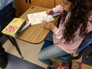 Student sitting at a desk with a worksheet observing what is happening in a cup.