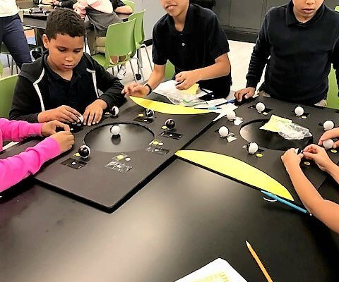 Students working at a table putting their moon phase models together.