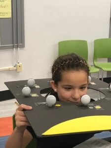 Student holding a cardboard moon phase diagram with a center cut to put her head through to observe the phases.