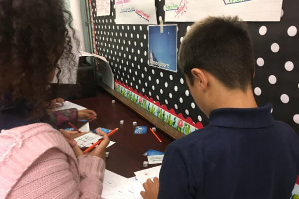 Students stand at a table rolling dice and reading cards.