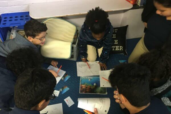 Student cluster around a piece of paper on the floor showing a picture of the ocean and roll die.