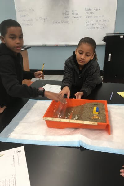 Students create waves with a water bottle in a model beach.