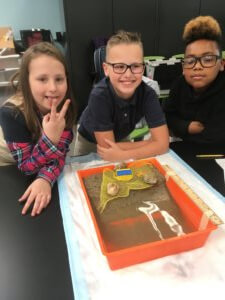 Students pose with their model beach.
