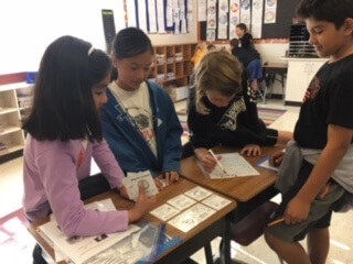 Students working at a table organizing cards.