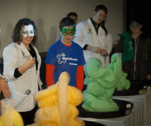 """Instructors and students look on as foam erupts from tall cylinder in an """"elephant toothpaste"""" demo."""