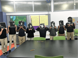 Students stand in the front of the room holding up images of a phase with different shadows on them.