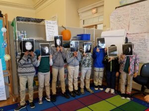 Students hold up photos showing a phase that model the moon phases.