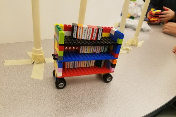 A Lego cart holding Lego dictionaries.
