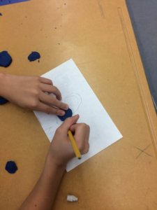 Hands trace playdough onto a topographic map.