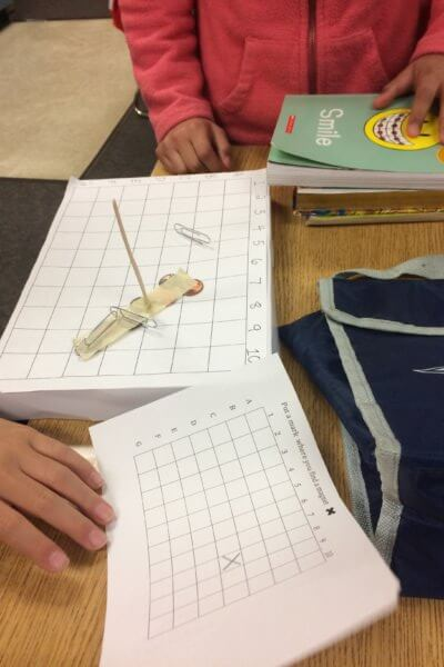 Students investigate magnetic items on a grid.