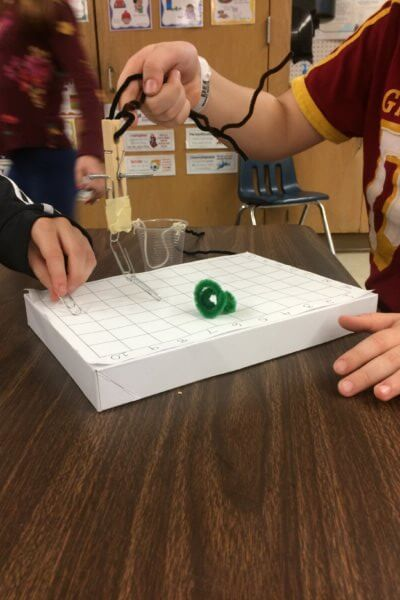Students investigate a magnetic board with paperclips.