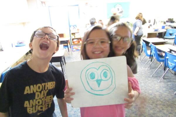 Three students are smiling at the camera, while one holds up a picture of an owl head.