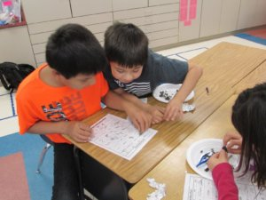 Students identify bones on a chart from an owl pellet.
